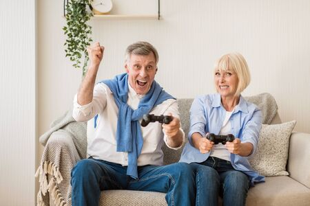 Mature couple competing in video games at home, having fun on weekends