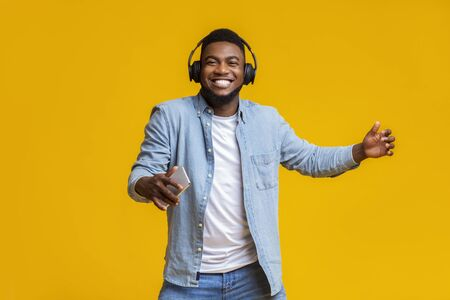 Happy black guy in wireless headphones listening music on smartphone and dancing, yellow studio background with free space Stock Photo