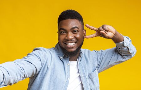 Say Cheese. Joyful black millennial guy showing peace sign while taking selfie, yellow studio background with free space Stock Photo
