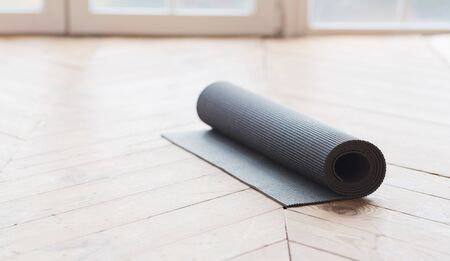 Sport equipment concept. Rolled up yoga mat on wooden floor at fitness studio, panorama with copy space Фото со стока