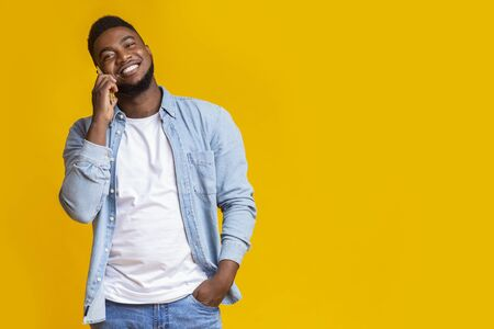 Portrait of carefree african american guy talking on cellphone on yellow background with copy space Stock Photo