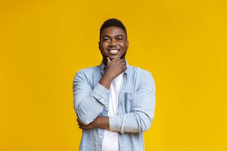 Portraif of handsome bearded african american man touching his chin and smiling over yellow studio background, copy space Stock Photo