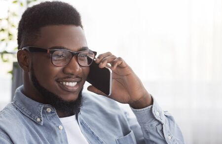 In touch. Handsome african american man in glasses talking on cellphone with somebody, copy space Reklamní fotografie