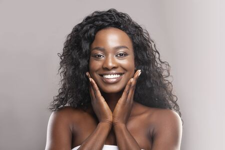 Rejuvenation concept. Beautiful african american woman touching her perfect skin on cheeks and looking at camera over grey background, free space