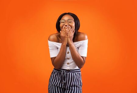 Positive African American Woman Laughing Covering Mouth With Hands Standing Over Orange Studio Background.