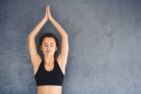 Woman exercising and doing yoga tree position with closed eyes over grey background, copy space