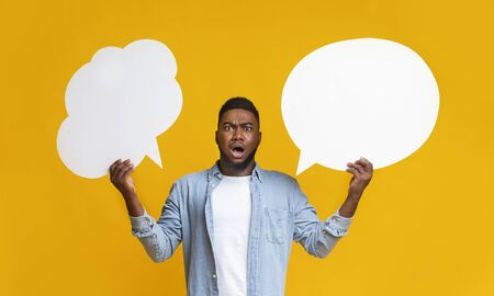 Complex choice. Confused black guy holding two speech bubbles on yellow background, panorama