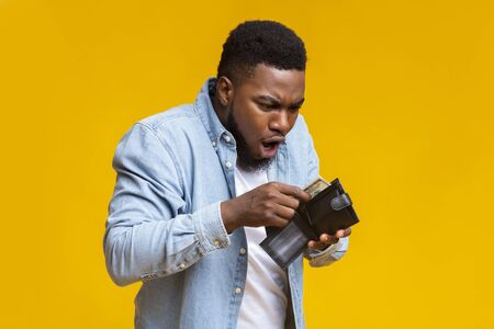 Wheres my money. Shocked african american guy holding wallet with dollar cash that will be not enough to cover spendings, yellow studio background.