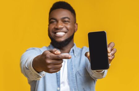 Check this app. Cheerful afro guy holding and pointing at smartphone with black screen, yellow background with free space