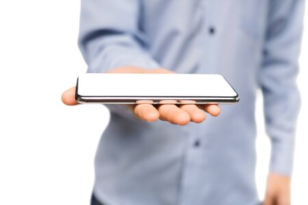 Unrecognizable man holding smartphone with blank white screen on open palm, selective focus on device