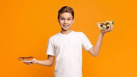 Choosing right or junk nutrition. Teenager holding fresh salad and chocolate donut like on scales, orange panorama background