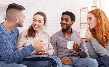 Joyful friends drinking tea and talking at home, enjoying their company