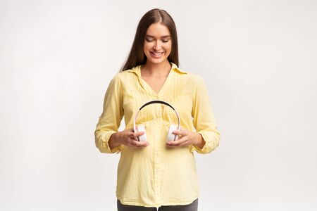 Pregnancy And Music. Smiling Pregnant Lady Holding Headphones Near Belly Standing Over White Studio Background. Empty Space Standard-Bild - 133676694