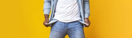 No money, no honey. Unrecognizable man demonstrating empty turned out pockets over yellow background, panorama Reklamní fotografie