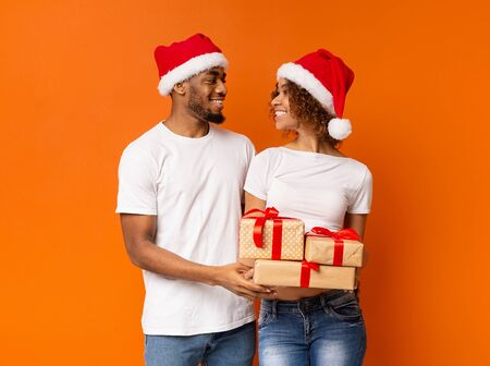 Happy couple ready for Christmas holidays. African-american man and woman standing with lots of presents, smiling to each other, orange background