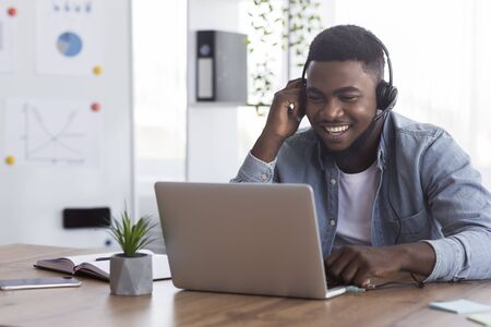 Cheerful african american worker wearing headphones, watching webinar on laptop in office