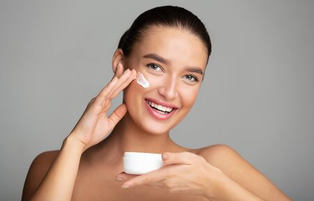Skincare and hydrating. Girl applying face cream, holding jar in hand over grey background Archivio Fotografico - 133378503