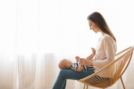 Lovely infant baby lying on lap of his mom that sitting in wicker chair at home, side view with free space