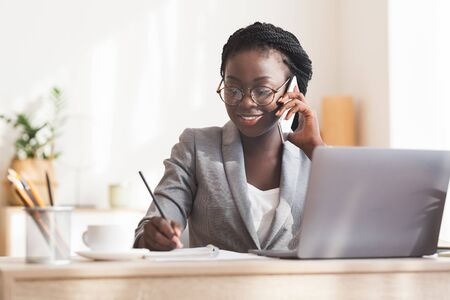 Smiling African American Secretary Talking On Phone And Taking Notes While Working On Laptop In Modern Office, Free Space