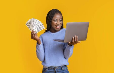 E-commerce and profit online. Young successful african american woman making money from internet, holding cash and laptop in hands, copy space, yellow studio background