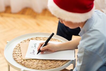 Xmas Gifts Wishlist. Boy Writing Letter To Santa Claus Sitting On Sofa At Home. Selective Focus Reklamní fotografie