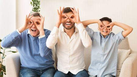 Grandfather, Father And Son Having Fun Holding Fingers Near Eyes Like Eyeglasses Sitting On Sofa Indoor. Panorama Reklamní fotografie