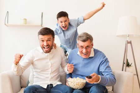 Excited Elderly Man, His Mature Son And Grandson Watching Sports On TV Shouting Celebrating Victory Sitting On Sofa Indoor