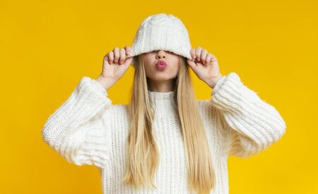 Playful blonde girl pulling down woollen white hat, showing kissing lips, yellow background