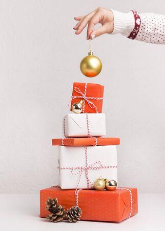 Conceptuel de Noël. Femme décorant l'arbre du Nouvel An de boîtes présentes sur fond blanc, panorama vertical