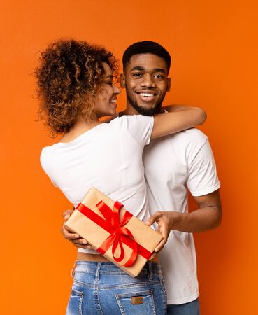 Cheerful black guy got present from his loving girlfriend, holding gift box and cuddling with woman, orange background