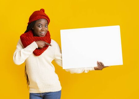 Smiling afro girl in red winter hat holding white blank advertising board and pointing at it over yellow background