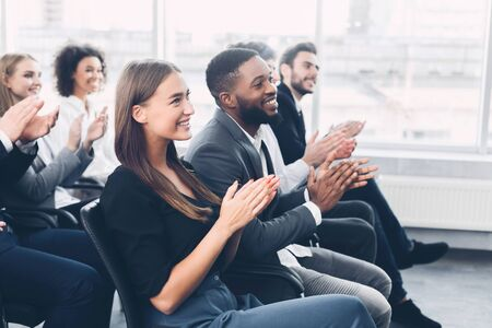 Group of business people applauding speaker after presentation in conference room