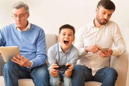 Stile di vita moderno. Ragazzo che gioca al videogioco seduto tra nonno e padre indifferenti a casa. Messa a fuoco selettiva