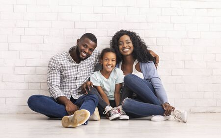 Happy Family Portrait. Cheerful african american parents and their little daughter sitting on floor and smiling together, white brick wall background.