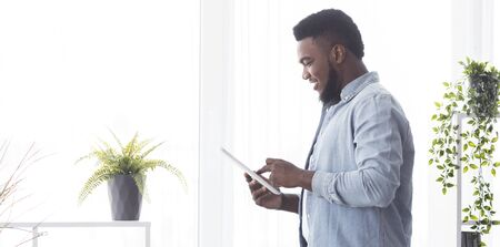 Cheerful african guy using digital tablet while standing near window at home, side view
