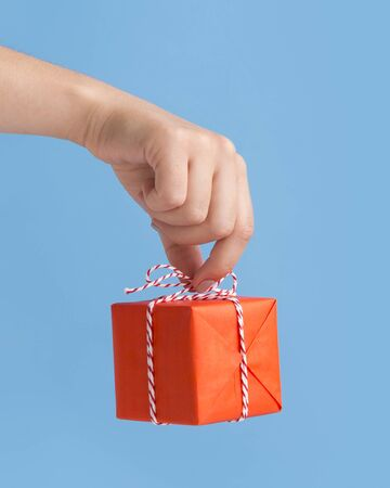 Close up of wrapped New Year box with presents in woman hand, blue background, copy space