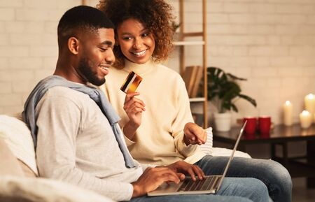 Happy spouses shopping online on laptop, ordering new clothes at home Stock Photo