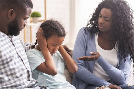 Family education. Little black girl closing her ears not to listen parents scolding Imagens