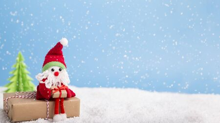 Winter wallpaper. Santa sitting on Christmas gift near tree over background with snowflakes, panorama, copy space Stock Photo