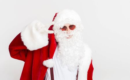 Merry Christmas and Happy New Year. Cheerful Santa smiling and showing v sign on white background, copy space