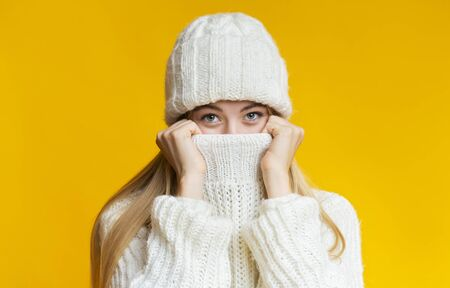 Blonde girl in winter clothes covering her face with sweater, warming up during cold season, yellow background