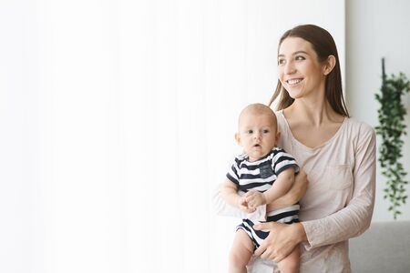 Joy of Motherhood Concept. Lovely young mother holding newborn baby in arms and looking out the window with blissful face expression