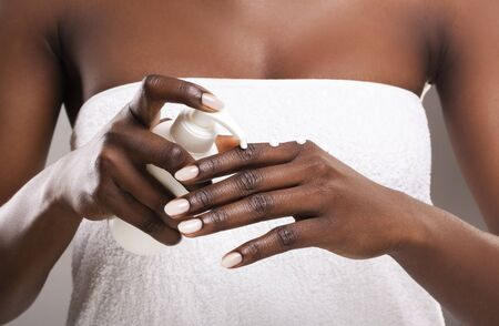 Closeup of african girl in white bath towel appying moisturising cream to her hands, crop