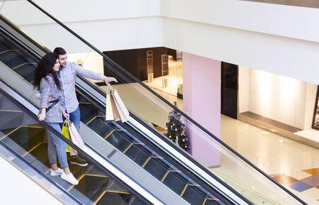 Vente et consommation. Couple descendant par escalator et pointant du doigt dans le centre commercial, espace libre