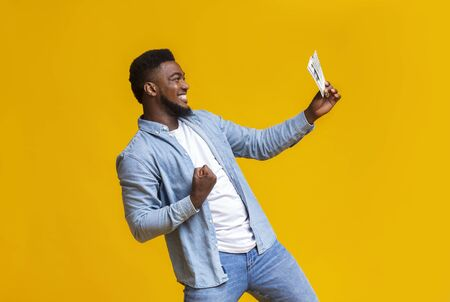 Im a winner. Joyful african american man holding few dollar bills celebrating lottery win, yellow studio background with copy space Banco de Imagens