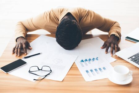 Business Crisis. Depressed Black Businessman Laying Head Down On The Desk With Papers, Having Stress