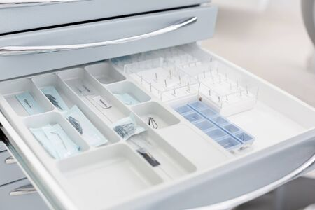 Close up of dental drill needles in open drawer, dental tools and equipment concept