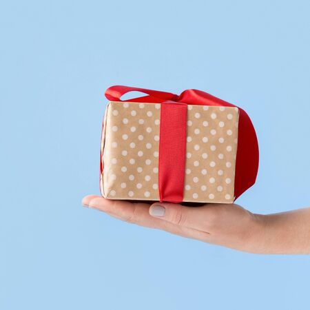 Small Christmas present in box wrapped in bow over blue background, copy space