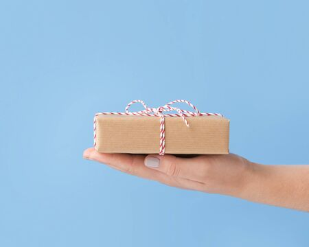 Christmas mail. Present box in cardboard on female palm, blue background, copy space