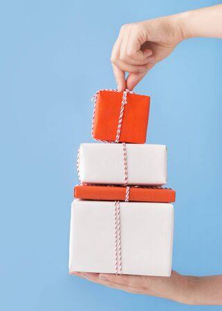 New Year cake of colored present boxes in woman hands over blue background
